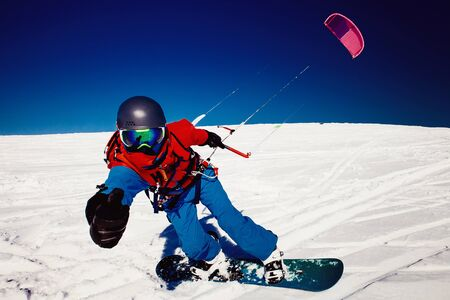 kiter: Snowboarder with kite on fresh snow in winter in tundra clear blue sky. Stock Photo