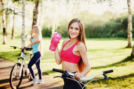 Close-up of girl holding sports bottle with water, looking camera, smiling, happy. Holds bicycle. In background blurred girl with a bicycle. Concept is use, norm of water for body, health.