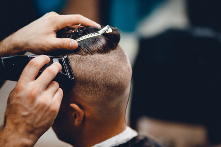 full length mirror: Male hippy customer in barbershop hairdresser on fashionable haircut, rear view. They cut her hair, put her hair dryer and wax. Concept of hair care. Toned photo. Stock Photo