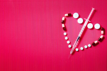Pills and syringe. Pills and syringe on red background in shape of heart. Copy space Stock Photo