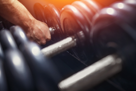 Close-up of a man takes a dumbbell in the gym. sun light