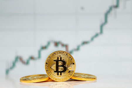 Gold Bitcoin on the background of the chart. Stock Photo