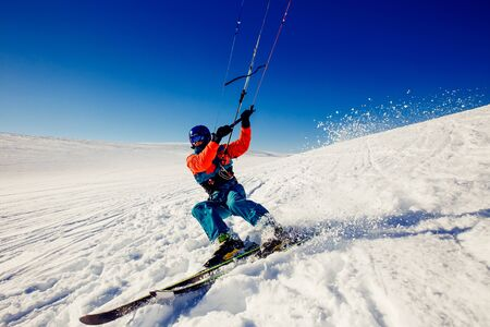kiter: Skier with a kite on fresh snow in the winter in the tundra of Russia against a clear blue sky. Teriberka, Kola Peninsula, Russia. Concept of winter sports snowkite on ski. Stock Photo