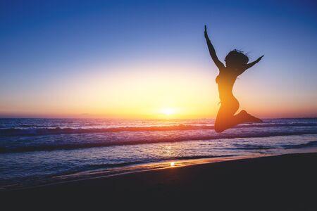 Silhouetten. Het meisje springt op strand met mooie zonsondergang op achtergrond Stockfoto