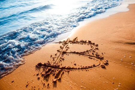 Icon bitcoin on golden sand, in background sea. Concept freelance, stock exchange. Stok Fotoğraf