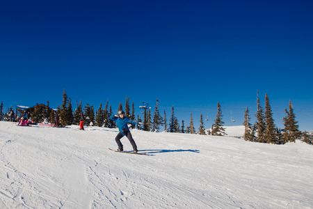 Sheregesh, Kemerovo region, Russia - April 16, 2016: Beginner snowboarder slides down the slope