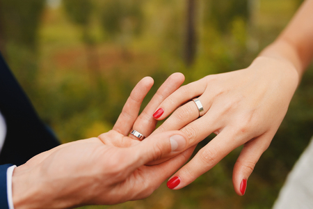 Marry me. Bride and grooms hands with wedding rings Stock Photo