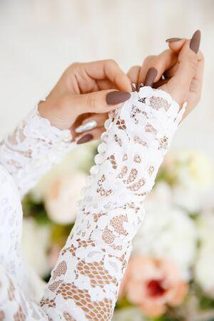 girl adjusts a wedding lace dress on her wrist