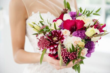 arm bouquet: wedding bouquet. The bride is holding flowers for the engagement.