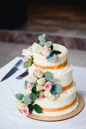 wedding cake with fresh flowers roses. three tiers Stock Photo