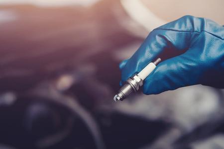 Mecánico automático mantiene las bujías en el guante Foto de archivo - 89410617