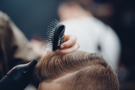 full length mirror: Barbershop. Close-up of a mans haircut, the master does the hair styling