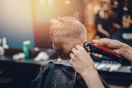 Barber shop. Barbershop little boy getting his head shaved by barber Stock Photo