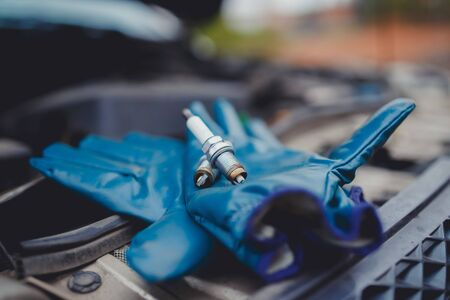 Spark plug. Car candles lie on gloves, in the background car service center