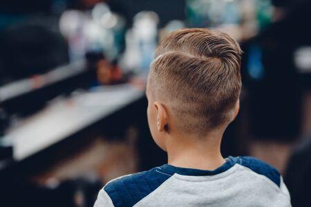 Friseur. Nahaufnahmebeispiel von Kindermode-Haarschnitt, Rückansicht im Friseursalon Standard-Bild
