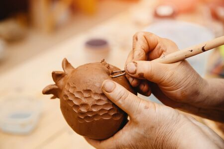 Ceramics. Master hands making a vase of grenades. Carves on the red clay