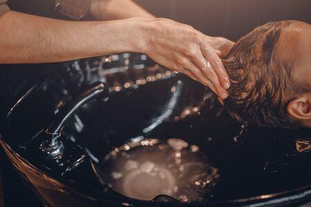 massage homme: Gros plan: un coiffeur lave la tête d'un client pour un homme