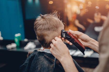Barber shop. Barbershop Hairdresser makes hairstyle a man with a beard child 스톡 콘텐츠