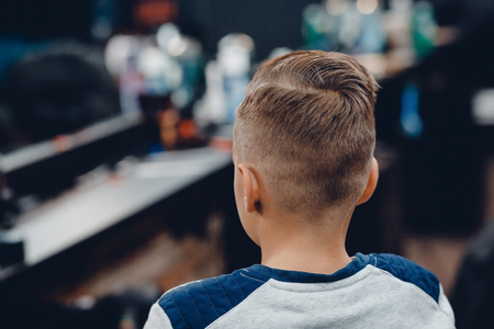 Barbershop. close-up example of childrens fashion haircut, rear view in barber shop Stock Photo