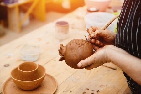Ceramics. Master hands making a vase of grenades Stock Photo