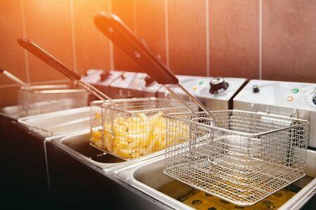 Pommes frites kochen. Gitter mit Streifen Hopfenkartoffel in kochendem Öl abgesenkt. Konzept des Schnellimbisses, köstliches Essen, Restaurant