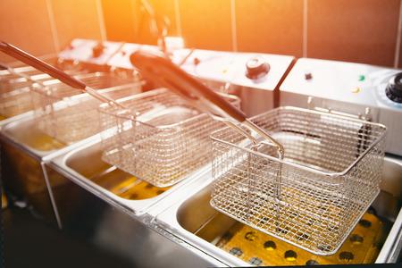 Bratpfanne für Kartoffeln mit kochendem Öl. Saubere Küche. Koncept Fast Food Restaurant, Ausrüstung Standard-Bild