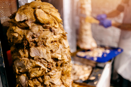 Chef prepares shaurma doner, stacked meat roasting. concept restaurant fast food