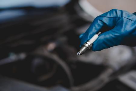 자동 정비공은 장갑에 점화 플러그를 유지합니다. 개념 자동차 진단 스톡 콘텐츠