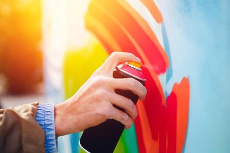 그의 손에 풍선 페인트와 예술가 낙서 벽에 그립니다.