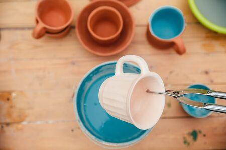 Ceramics. master applies a glaze on the clay mug