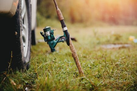 Fishing. Close-up of a fishing rod with a spinning rod for catching fish, stands near the wheel of the car. Concept travel, recreation for men
