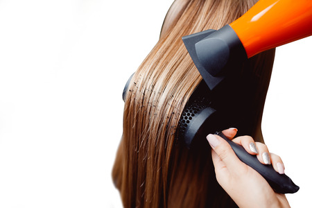 master in a hairdresser dries her hair to a girl with a hairdryer and makes a styling, isolated background Banco de Imagens