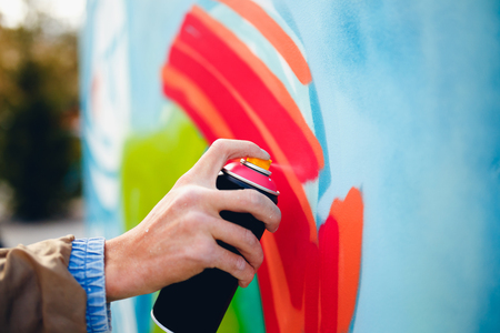 Artist graffiti with a balloon paint in his hands draws on the wall