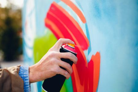 Kunstenaar graffiti met een ballon verf in zijn handen trekt op de muur Stockfoto