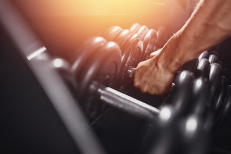 Dumbbell. Close-up man grabs a heavy dumbbell in the gym with his hand. Concept lifting, fitness. Stock Photo