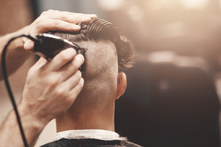 full length mirror: Barber shear hair electric car to a young guy hipper hair for a fashionable hairstyle. Concept hair salon, barbershop. Stock Photo