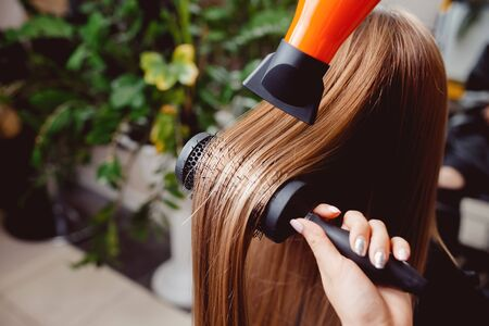 美容師のマスターはヘアドライヤーで女の子に彼女の髪を乾燥させ、スタイリングを行います