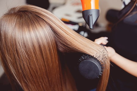 Stylist puts a hair dryer and comb hair in a hairdresser