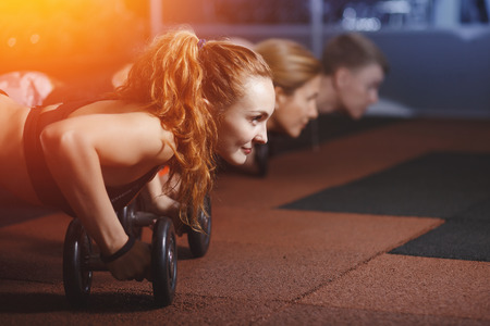 lifting. Group of athletes doing training plank ups with kettlebells in gym Stock Photo - 90439184