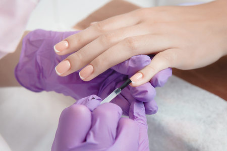 Manicure. Master master does nail delicate French manicure
