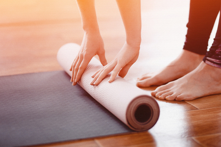 Yoga. Close-up woman folding roll fitness or yoga mat after working out home in living room. Concept healthy life.