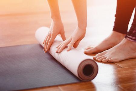Yoga. Primer plano mujer plegable rollo fitness o yoga mat después de hacer ejercicio a casa en la sala de estar. Concepto de vida saludable.
