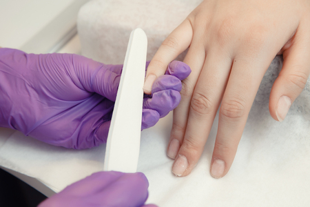 Master removes shellac gel nails with sawing tool. Concept manicure.