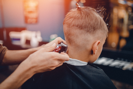 Barber shop. Barbershop Hairdresser makes hairstyle a man with a beard child 写真素材