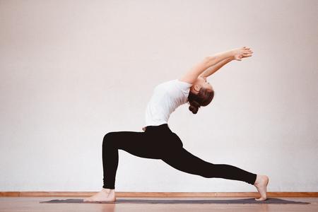 Yoga concept. Sluit omhoog vrouw mediteert terwijl het uitoefenen van yoga in opleidingszaal of huis.