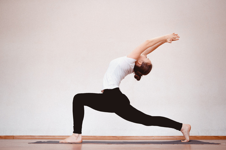 Yoga Concept. Close up woman meditates while practicing yoga in training hall or home. Standard-Bild