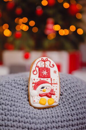 Gingerbread new year. Gingerbread on glowing lights of a Christmas tree. Concept of sweets and gifts