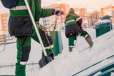 Team of male workers clean roof of building from snow with shovels in securing belts of mantra. Stock fotó