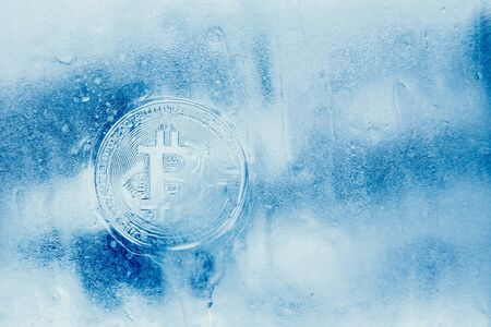 Bitcoin. Icon bitcoin on a blue ice frozen background