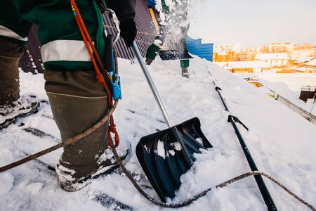 Team of male workers clean roof of building from snow with shovels in securing belts of mantra. Stock Photo